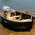 Coracle 250 showing (optional) 7ft oars, chrome rowlocks; Torqeedo 1003 on transom.