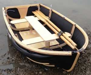 Nautiraid Coracle 250 with rowing upgrade (longer oars and chromed metal rowlocks); optional longitudinal centre seat with second set of chromed metal rowlocks; non-slip strips on floorboards and seats (they are translucent, and in this photo easiest to see on the floorboards). The centre seat option makes the fore and aft trim almost perfect when rowing on your own, below.